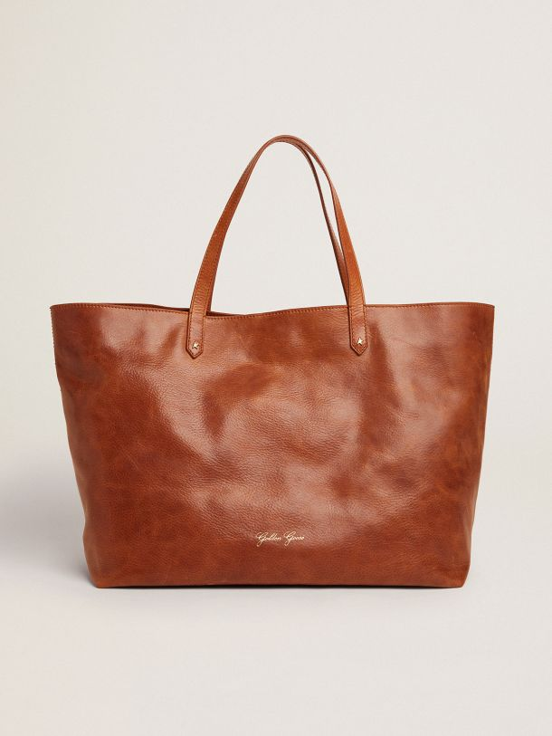 Tan-colored Pasadena Bag with gold logo on the front